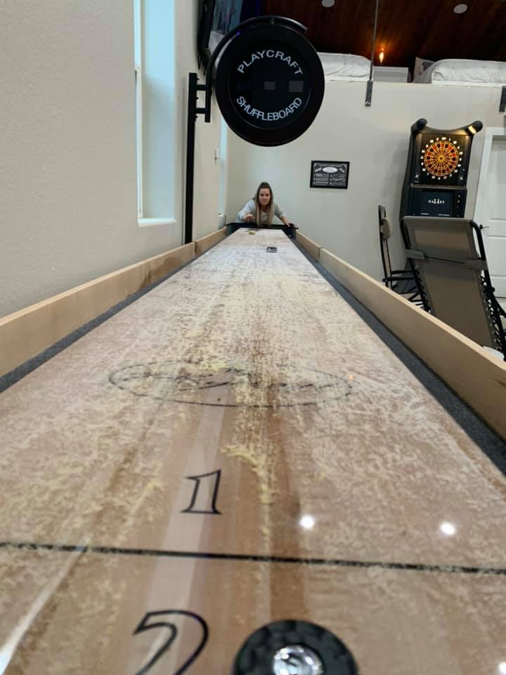 Woman playing a shuffleboard game in a game room.| Adult Summer Vacation on Lake LBJ