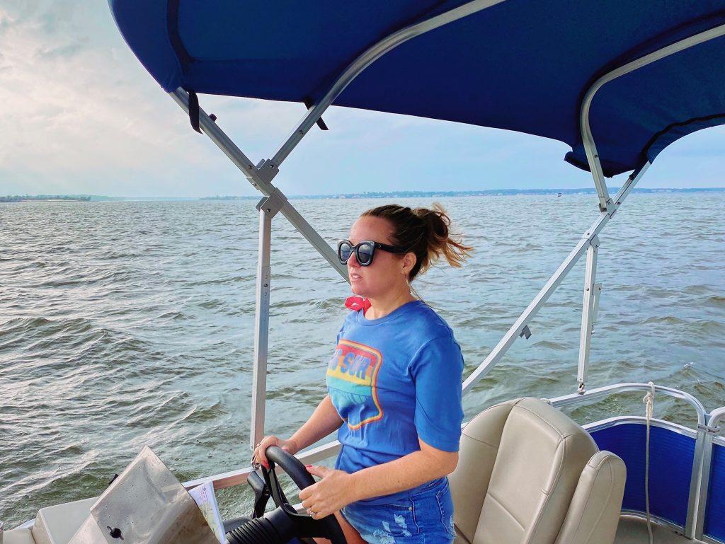 Woman driving a pontoon boat on the water. | Margaritaville Lake Resort, Lake Conroe