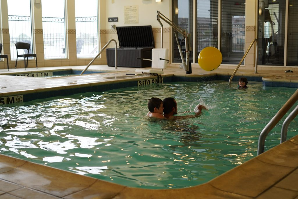 Man with kids playing in the swimming pool.   A Guide to Granbury, Texas