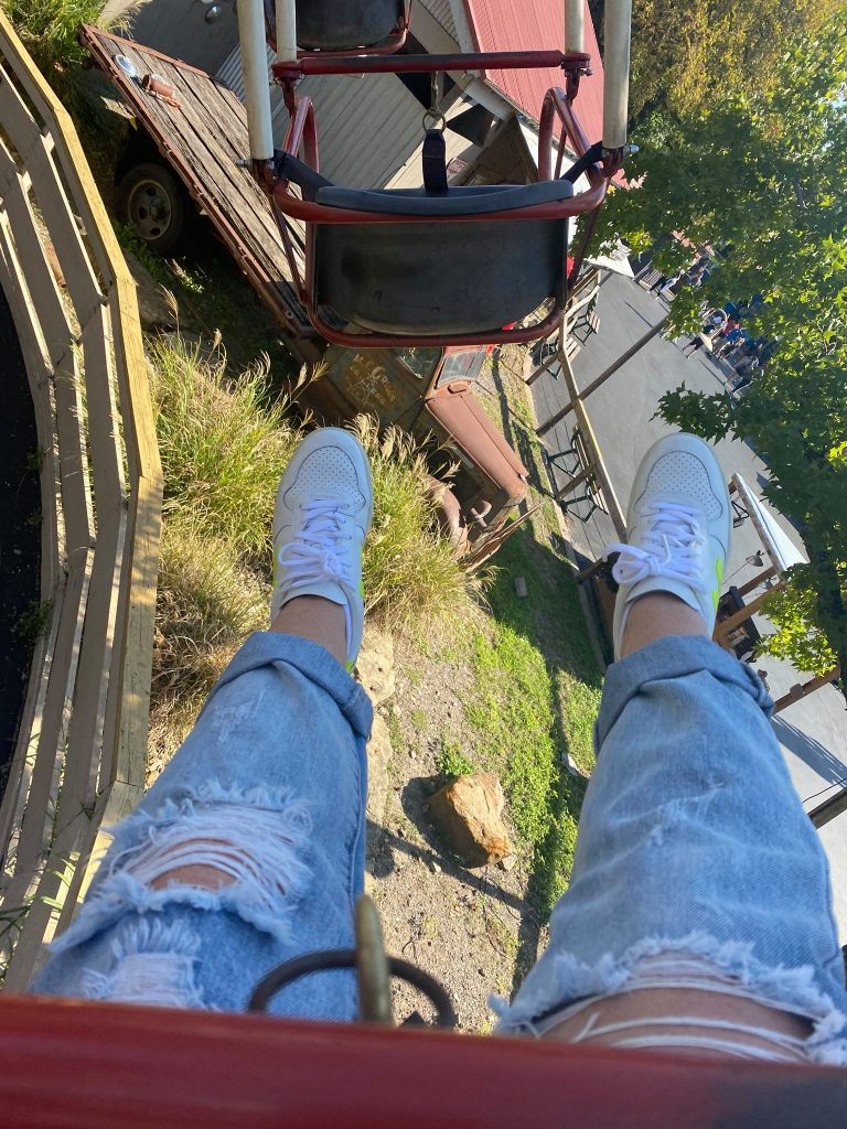 Woman's feet above ground on a ride at Six Flags.   Guide to Six Flags over Texas Hallowfest