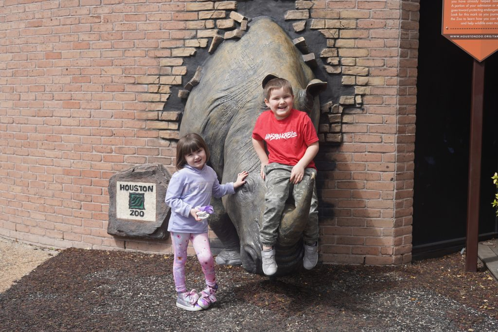 Kids posing on the rhino statue at the zoo. | The Houston Zoo