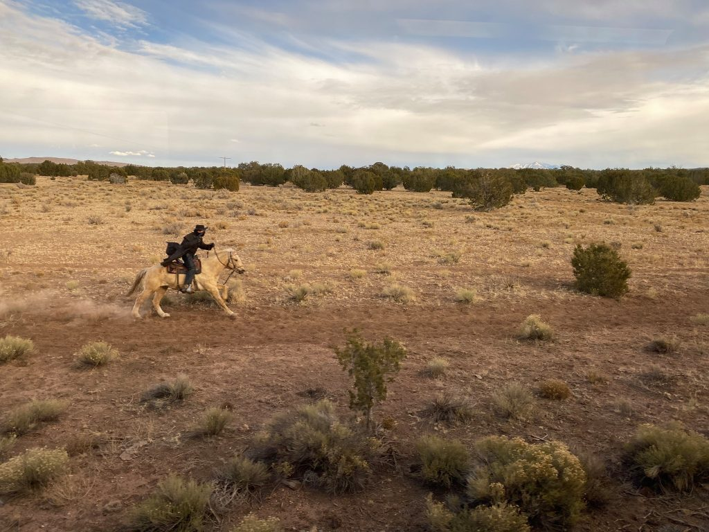 Role play robbery with man riding a horse in the desert during the grand canyon railway train ride. | Grand Canyon Railway in Arizona