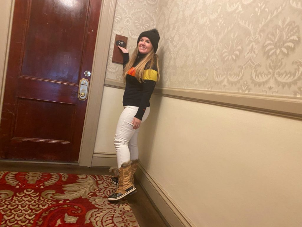 Woman smiling standing in front of Room 217.   Stay at Stephen King's The Shining Hotel - Also known as the Stanley Hotel
