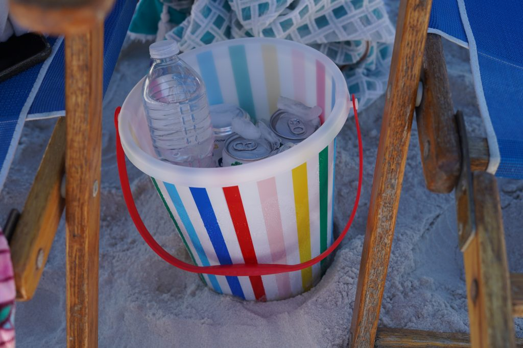 Colorful sand bucket  with drinks inside on the beach.   Guide to Gulf Shores & Orange Beach Alabama