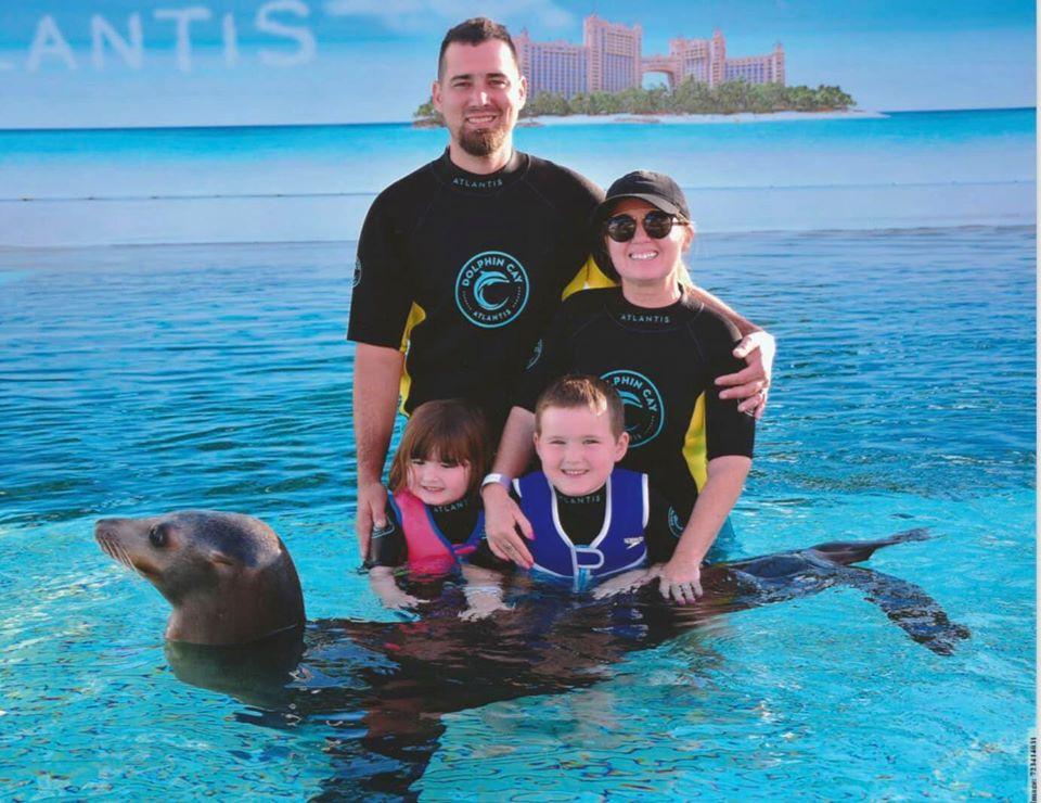 Family posing with sea lion in the water at the Atlantis resort.   Atlantis, Bahamas