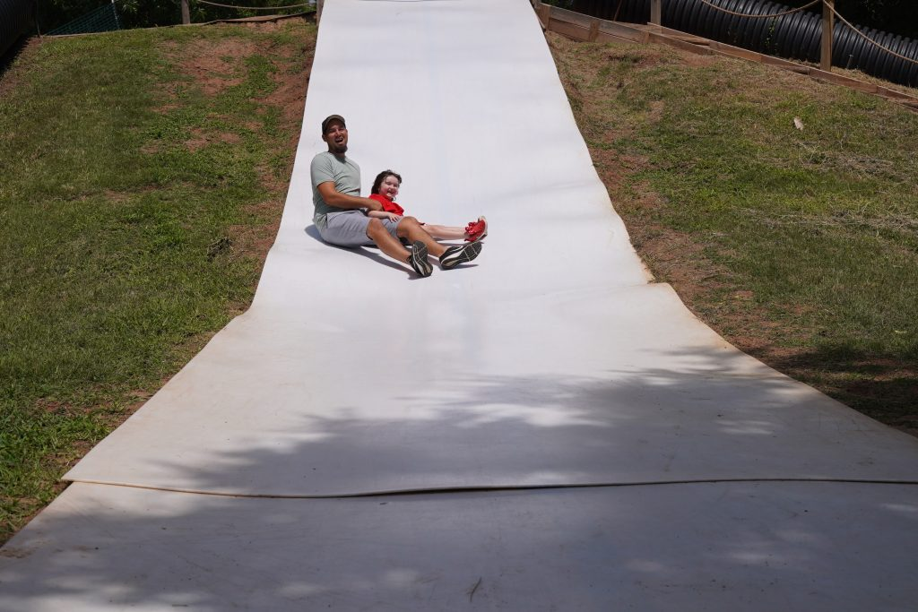 Man with little girl going down the slides on Slide Mountain at Blessington Fields. | Blessington Farms in Simonton, Texas