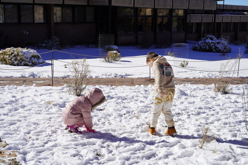 Two kids playing in the snow at the Grand Canyon. | Arizona Itinerary with Kids