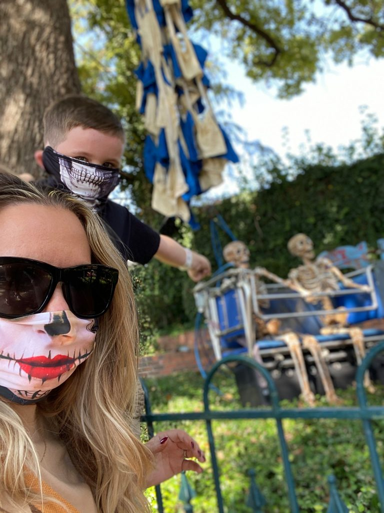 Woman and little boy taking a selfie with two skeletons blurred in the background.   Guide to Six Flags over Texas Hallowfest