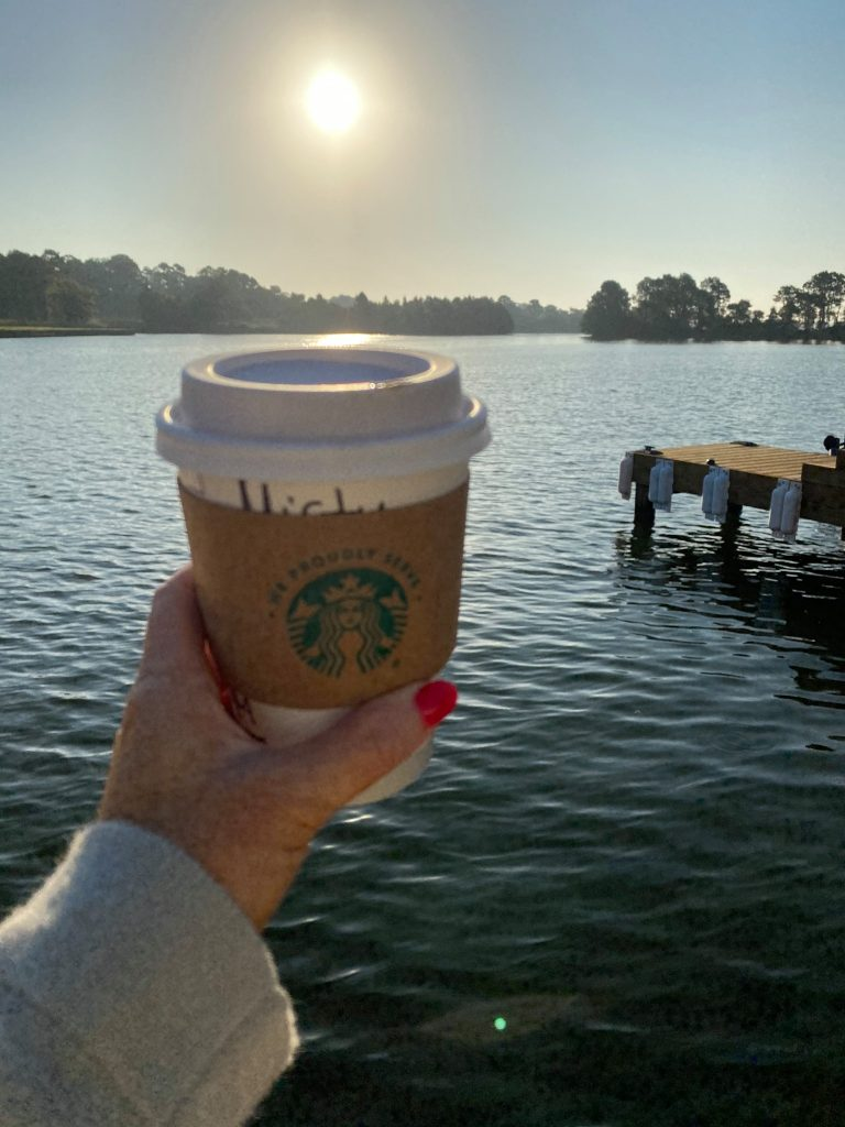 Woman holding a small Starbucks cup with the water and sunrise in the background. | Margaritaville Lake Resort, Lake Conroe