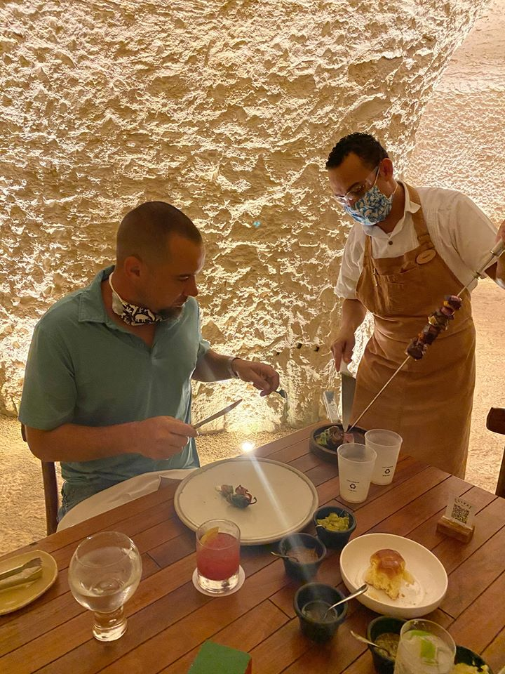 A man being served by a waiter at a restaurant.   Guide to Hotel Xcaret in Mexico