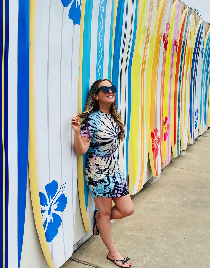 Woman smiling and posing leaning up against a wall of colorful surf boards. | Margaritaville Lake Resort, Lake Conroe