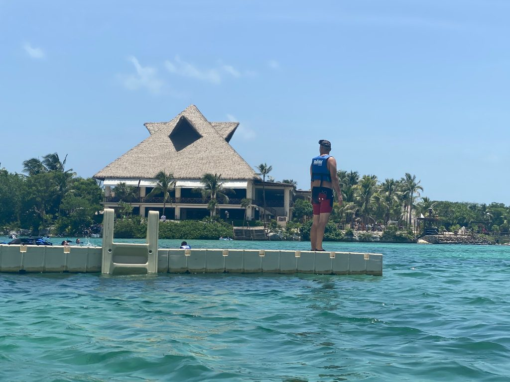 Man standing on the pier above the water. | All About XeI-Ha Park in Riviera Maya