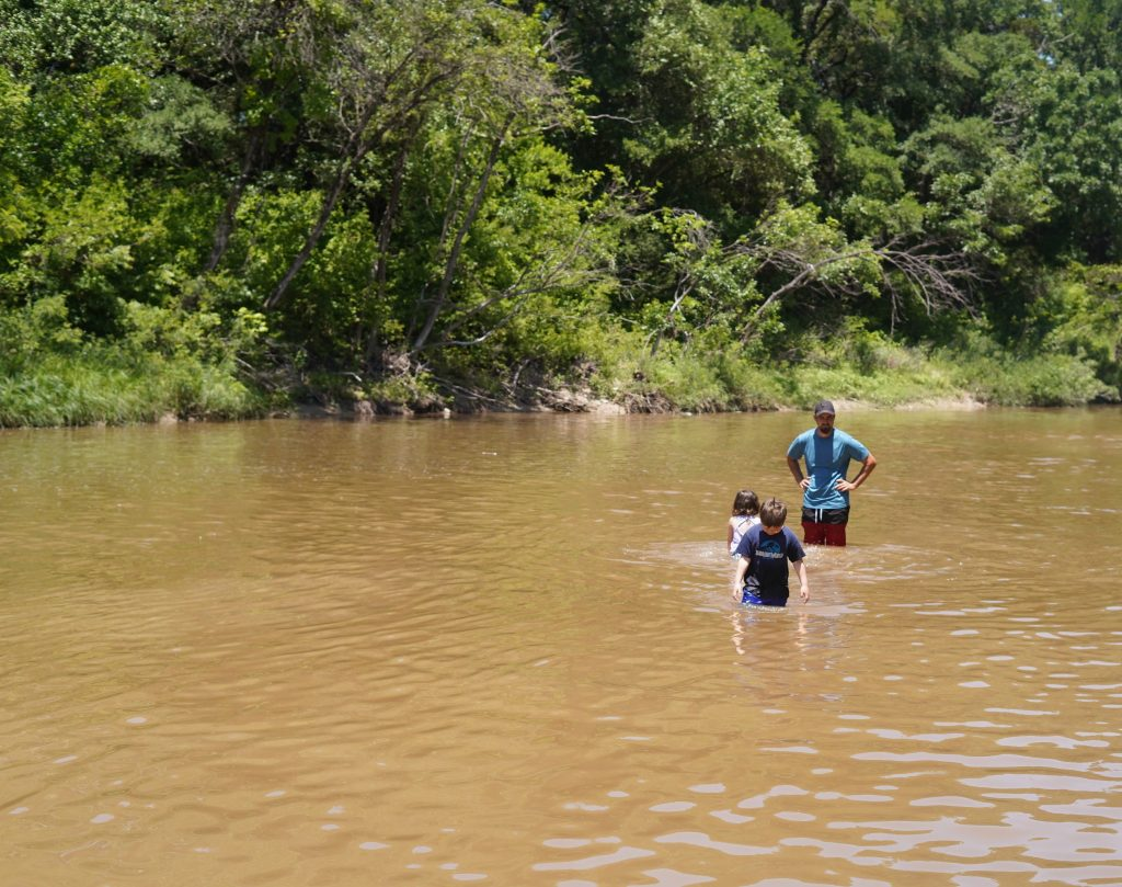 Man with his kids swimming in the Paluxy river.   Dinosaur Valley State Park in Texas