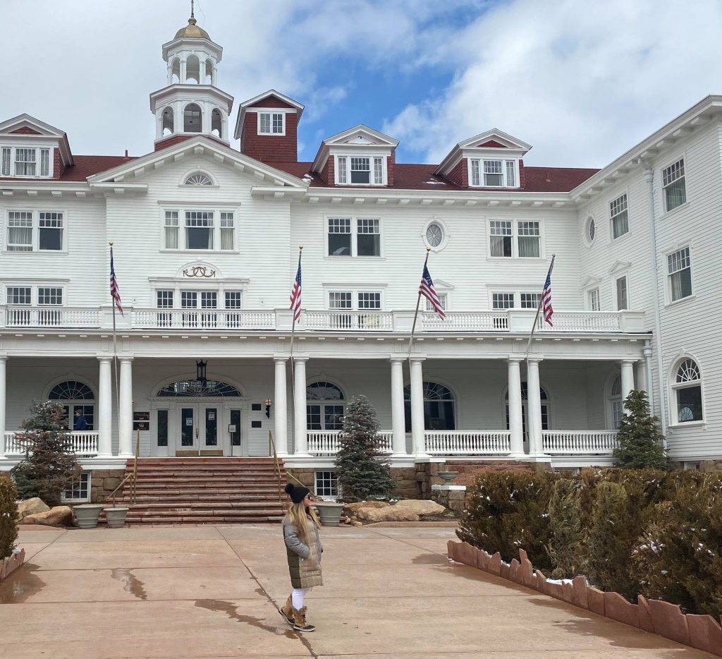 Woman standing in front of the Shining Hotel.   Stay at Stephen King's The Shining Hotel - Also known as the Stanley Hotel