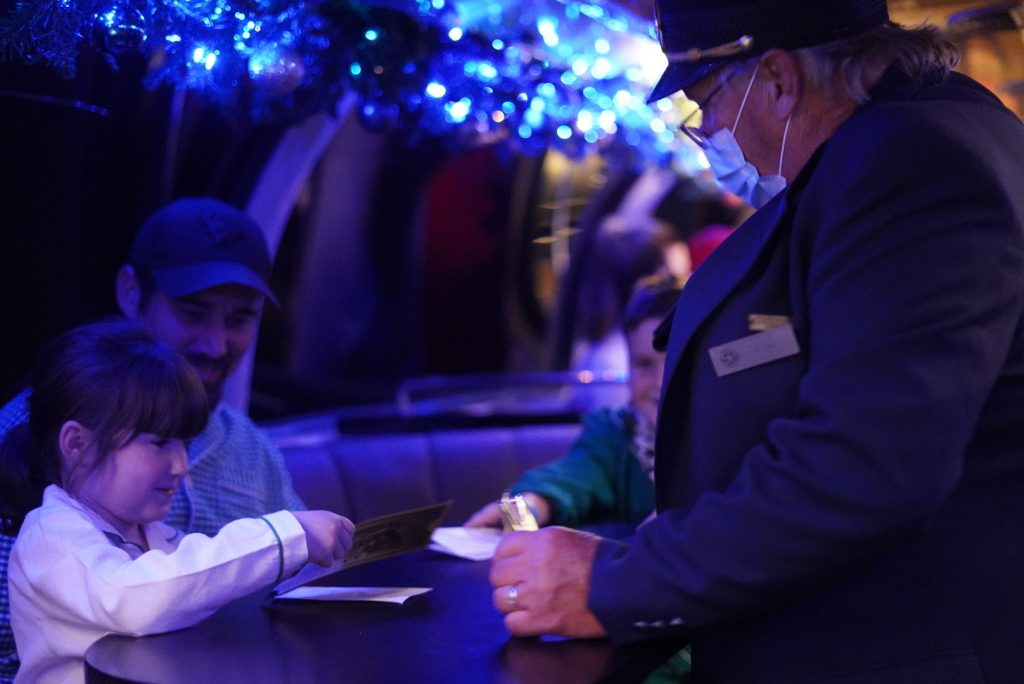 Conductor checking the tickets of a little girl and man on the Polar Express train ride. | The Polar Express Train Ride in Palestine, Texas