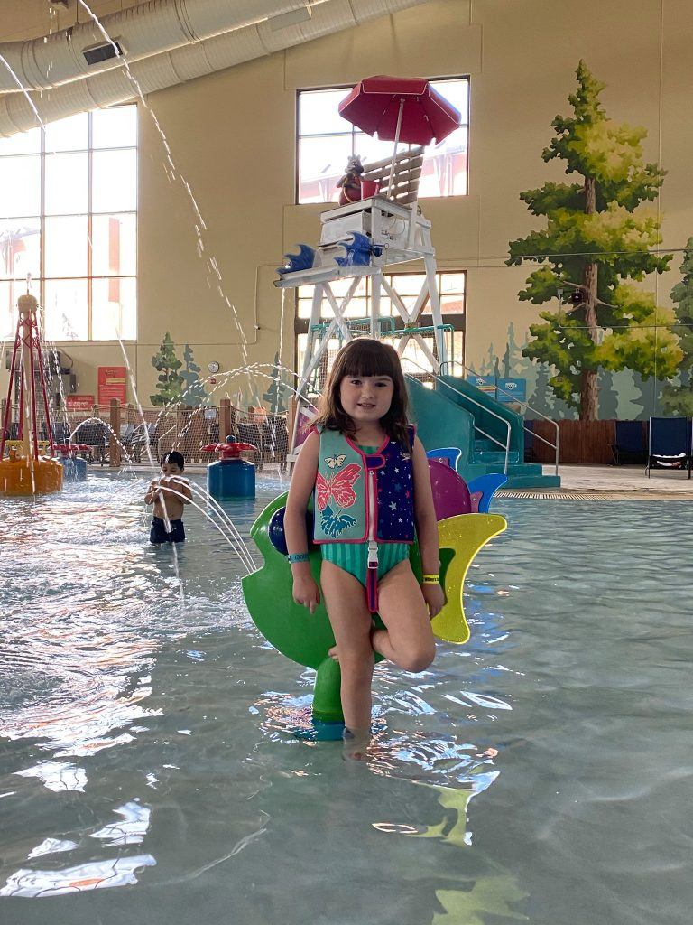 Little girl with a lifevest and bathing suit on playing in the toddler area of the waterpark.  Great Wolf Lodge in Grapevine, Texas