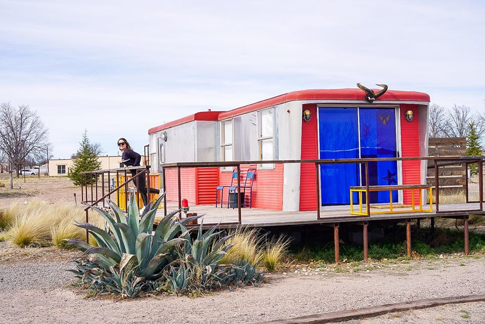 El Cosmico trailer with woman on patio in Marfa. | Marfa, Texas- Where to Stay, What to do, & What to Eat