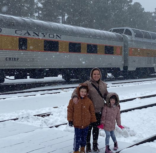 Woman with two kids standing in the snow in front of the grand canyon train. | Williams, Arizona on Route 66 with Kids