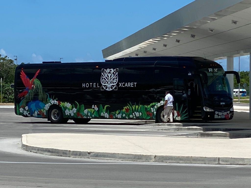 Large black transportation bus parked outside hotel.   Guide to Hotel Xcaret in Mexico