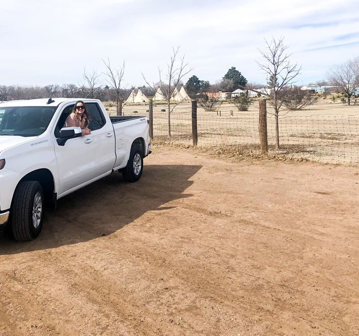 Truck on the dirt road with woman leaning out of the window. | Marfa, Texas- Where to Stay, What to do, & What to Eat