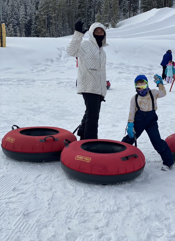 Man and child waving and tubing on Copper Mountain.| Guide to Copper Mountain Resort in Colorado