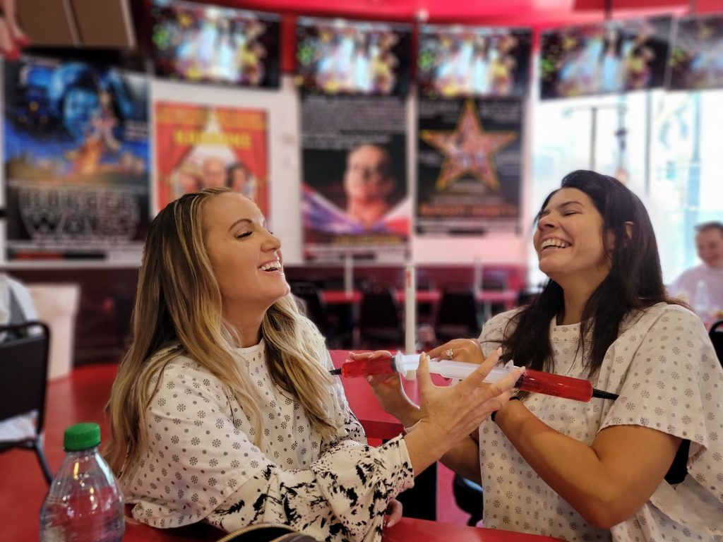 Two women laughing and posing with shots pushed into their arms.   Where to eat in Las Vegas