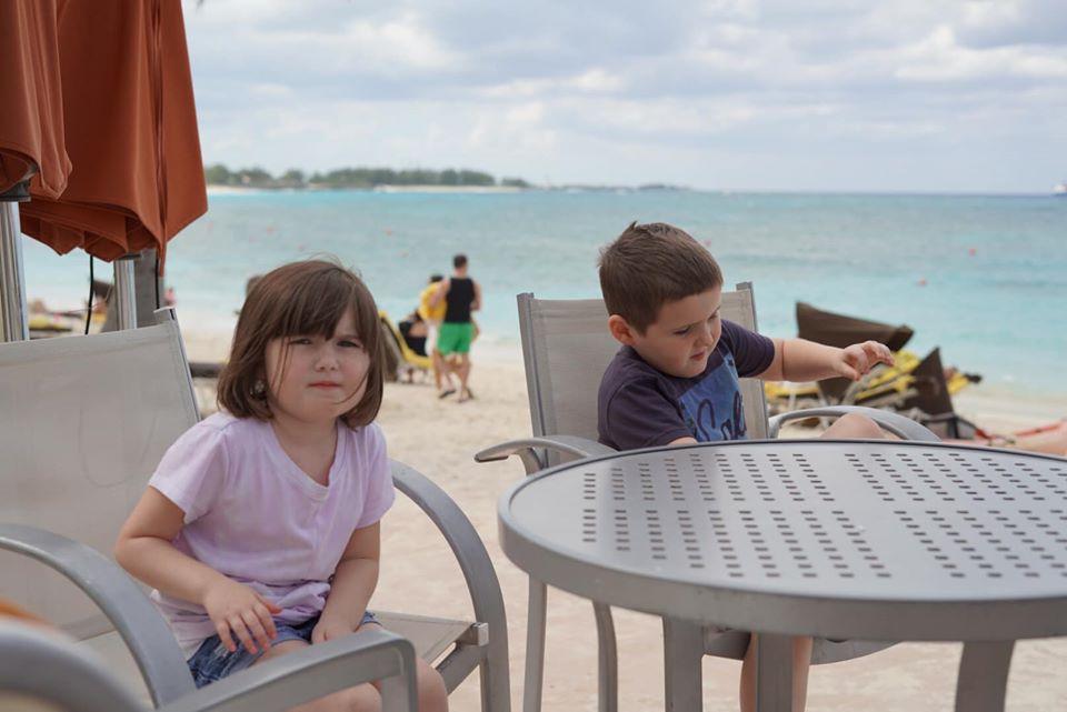 Kids sitting at a table at the restaurant at the reef pool at the Atlantis resort.   Atlantis, Bahamas