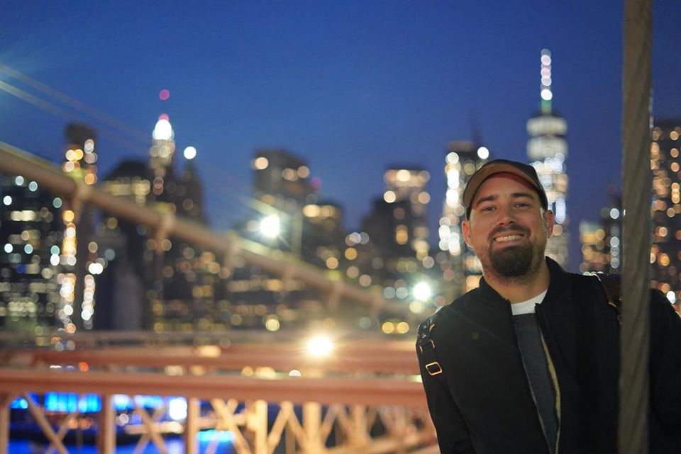 Man posing with a view of the Brooklyn Bridge at night.   New York City