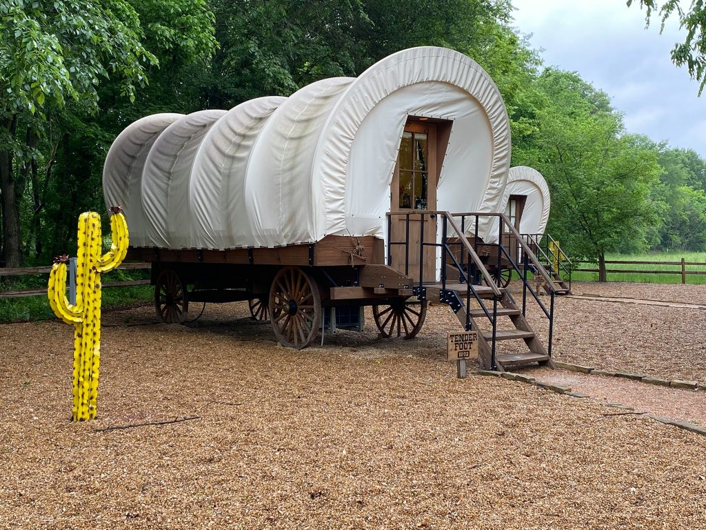Covered wagon with steps and a fake yellow cactus. | Glamping at Silver Spur Resort in Canton, Texas