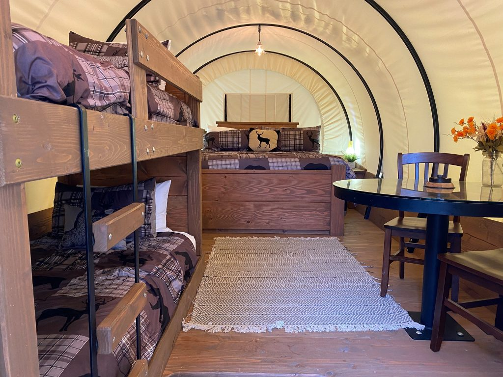 Inside of covered wagon with bunk beds, table and queen sized bed. | First Monday Trade Days in Canton, Texas
