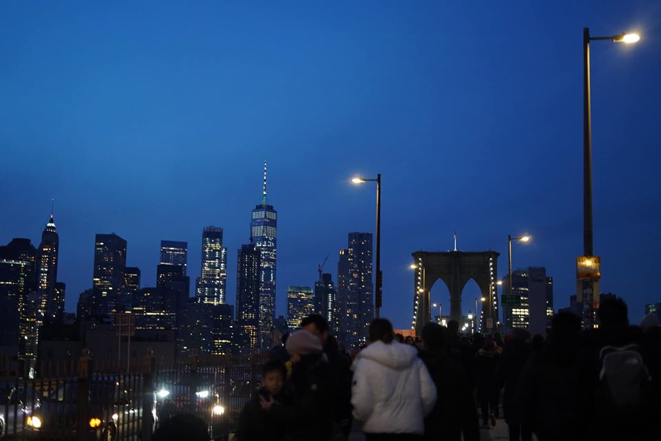 People walking across the Brooklyn Bridge at night.   New York City