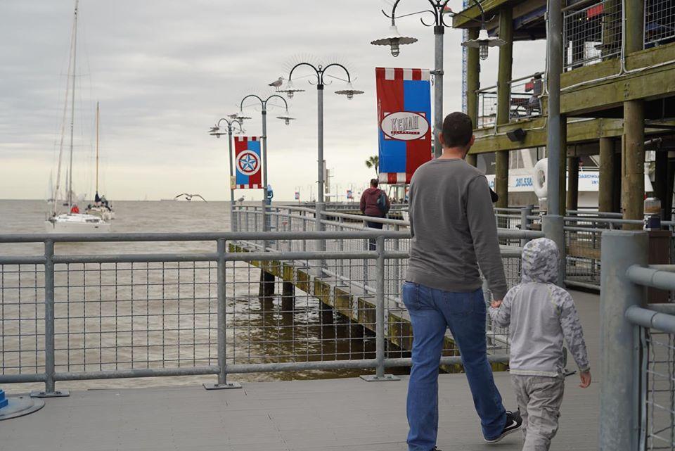 Man walking with little boy down the boardwalk at Kemah Boardwalk. | Kemah Boardwalk in Texas