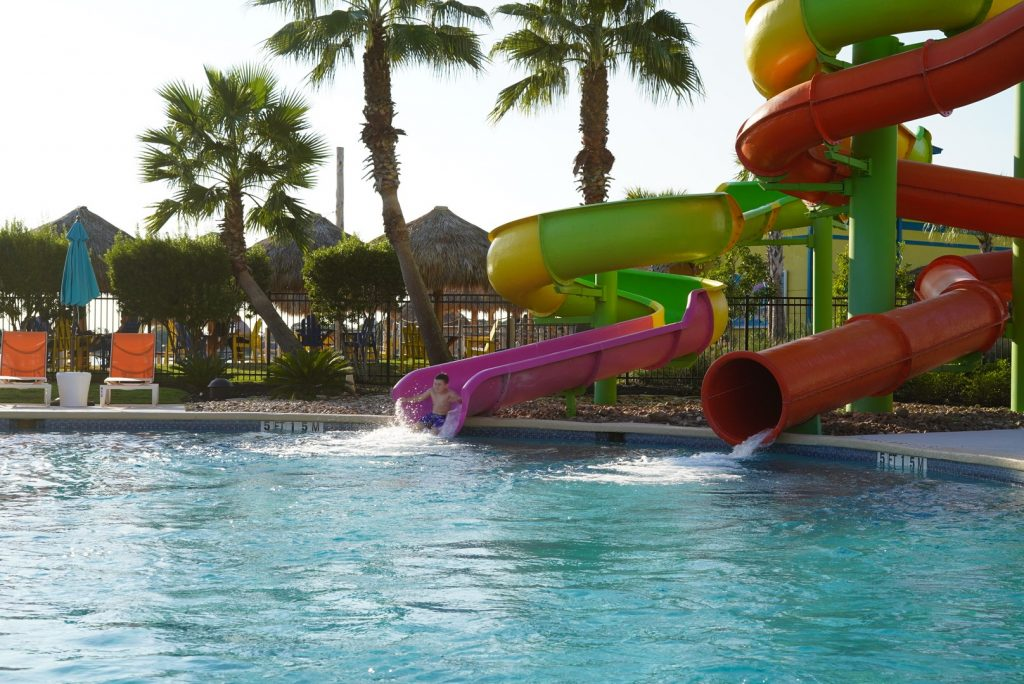 Little boy splashing into the pool after coming down a big waterslide at the waterpark. | Margaritaville Lake Resort, Lake Conroe