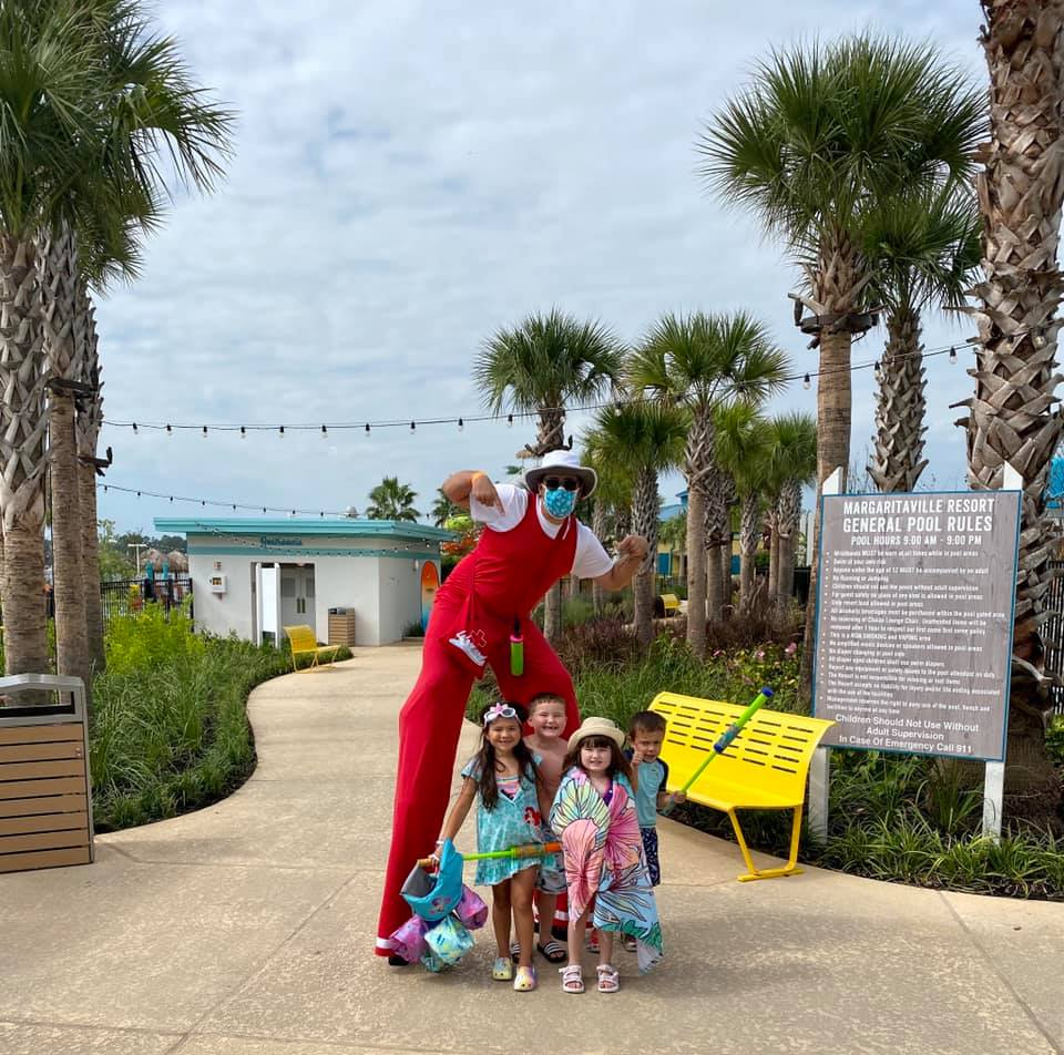 Four kids and a tall man of stilts posing at the waterpark. | Margaritaville Lake Resort, Lake Conroe