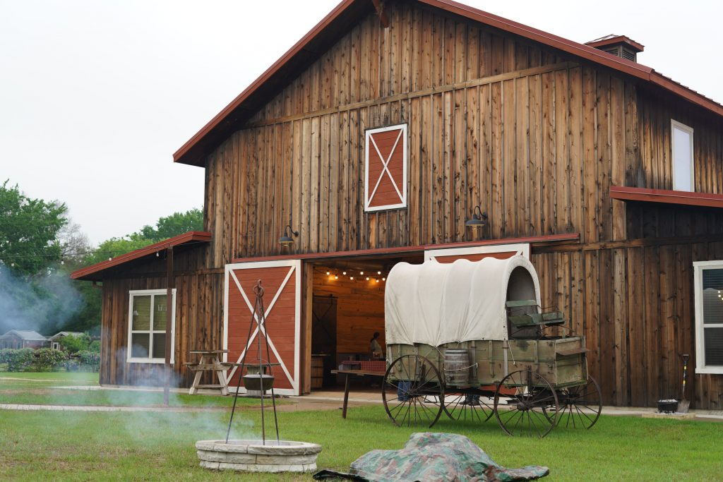 Large barn with covered wagon in front of it. | Glamping at Silver Spur Resort in Canton, Texas