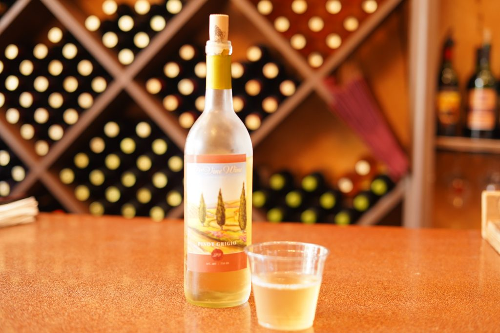 Bottle of wine with a cup of wine on a bar.   A Guide to Granbury, Texas