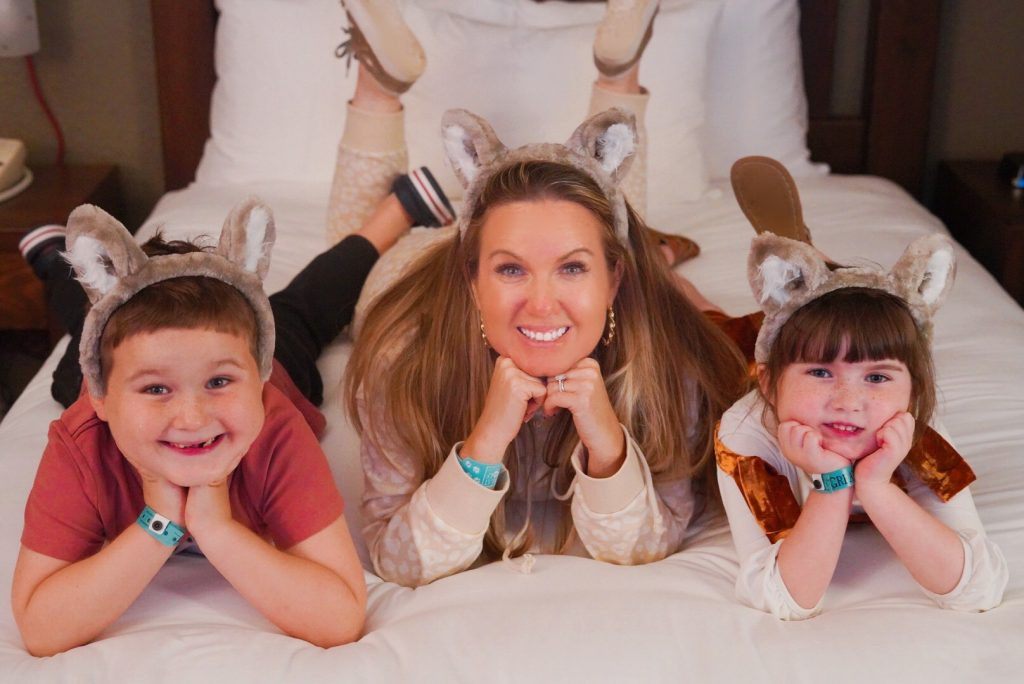 Woman with her two kids laying on a bed smiling at the camera wearing wolf ears on their heads.   Great Wolf Lodge in Grapevine, Texas